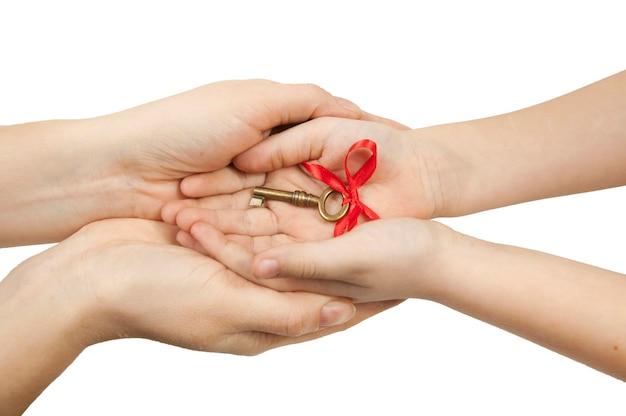 隔離された白い壁の手のひらの上で手に赤い弓を持つヴィンテージの鍵、ホームレスに住宅を与えるという概念