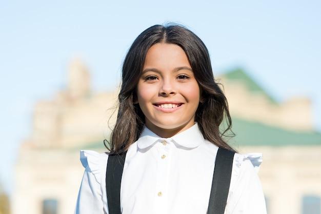 빈티지 아이 패션과 뷰티. 고급스러운 복고풍 제복을 입은 여학생. 공부할 준비가 된 작은 행복한 소녀. 오래된 학교. 학교로 돌아가다. 어린 시절의 행복. 세련된 유니폼 시장. 똑똑한 모습. 항상 웃고 있습니다.