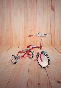 Vintage kid red tricycle on wood background.