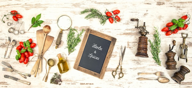 Vintage kitchen utensils with red tomatoes and herbs. blackboard with sample text herbs & spices