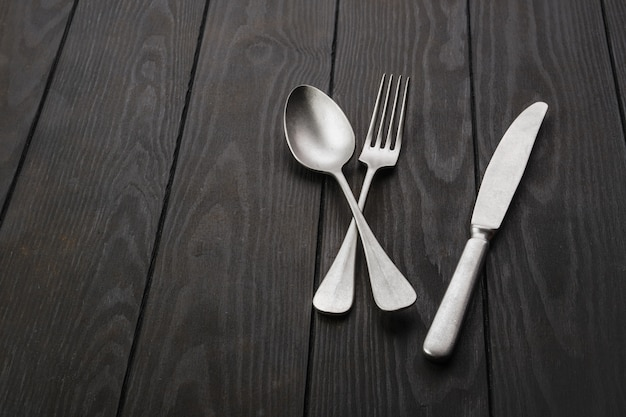 Старинный нож возле вилки и ложки на темном деревянном столе