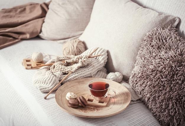 Ferri da maglia vintage e filati con una tazza di tè