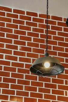 Vintage lamp hanging from the ceiling with light on the brick wall.
