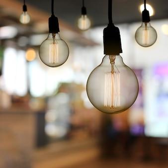 Vintage lamp or modern light bulb hang on ceiling in the restaurant.