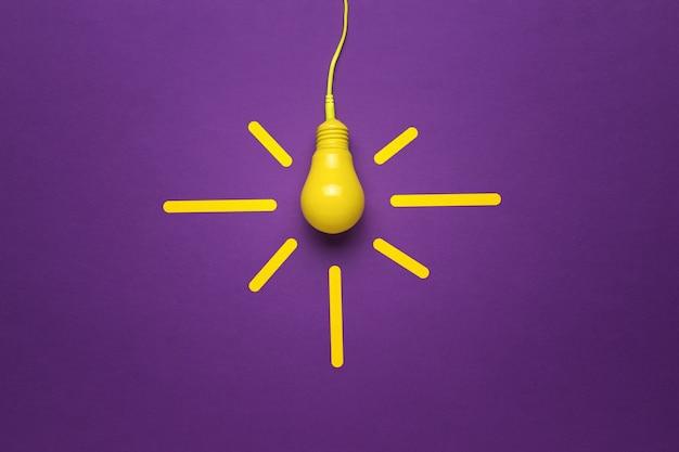 Винтажная лампа на проводе на фиолетовом фоне. минимализм. концепция энергетики и бизнеса. плоская планировка.