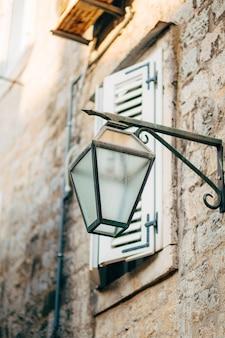 Старинная лампа на стене на улице