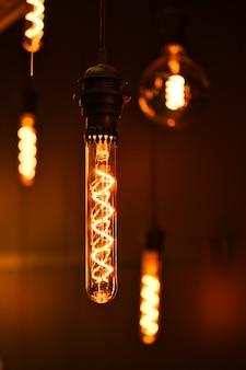 モダンなインテリアのための暗い背景にタングステン糸が入ったガラスフラスコのヴィンテージランプ。