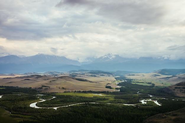 曇り空の下で雪に覆われた山の尾根を背景に山の川と森の広大な高原とヴィンテージの風景。地平線上の低い雲の間の緑の山の谷と雪の山脈。