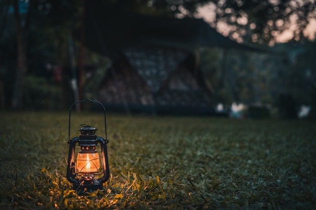 Vintage lantern on the grass while camping in the evening