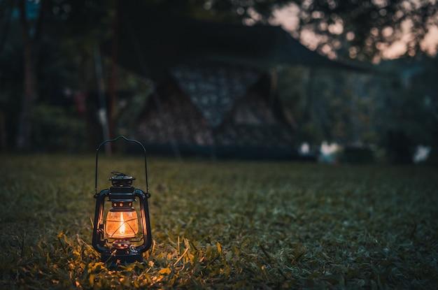 夕方にキャンプしながら草の上のビンテージランタン