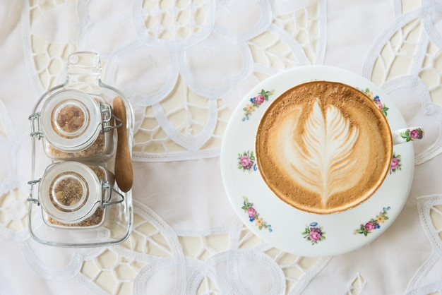 Vintage latte art coffee on table with sugar
