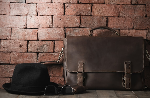 Vintage leather bag and hat on wood table