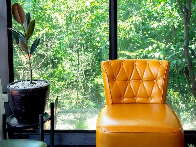 ヴィンテージの革張りのソファ、大きなガラス窓の植木鉢の近くにピンとボタンの装飾が施された黄色、外の緑の自然の景色。