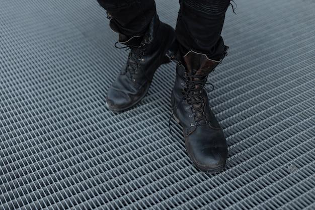 Винтажные кожаные стильные черные сапоги крупным планом на мужских ногах. старомодный стиль.