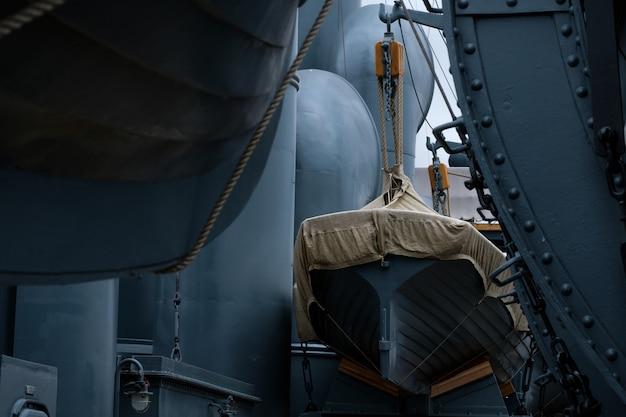 Старинные спасательные шлюпки на синем металлическом военном корабле