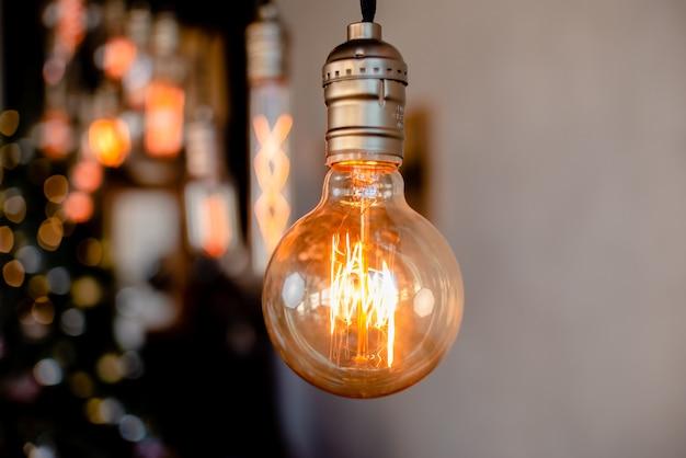 明るい灰色の抽象的な背景に掛かっているヴィンテージの電球。水平ビューcopyspace