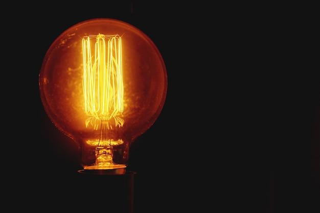 Винтажная лампочка на черном фоне с копией пространства