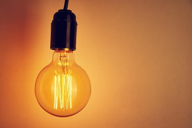 오렌지 복사 공간에 빈티지 전구입니다. 빛나는 에디슨 전구
