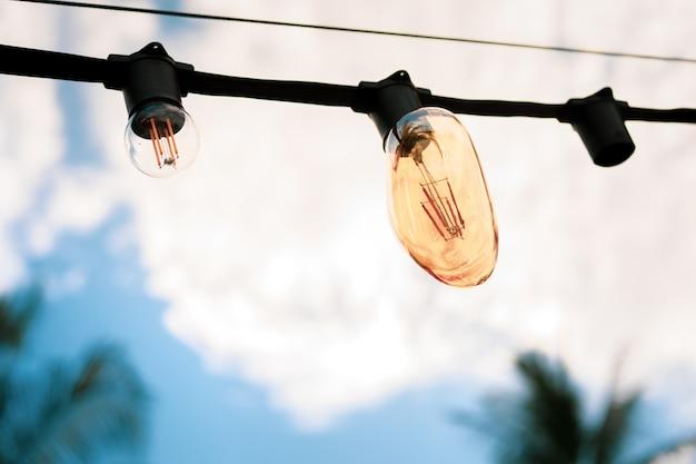 ビーチフェスティバルでケーブルからぶら下がっているヴィンテージ電球をクローズアップ、ヴィンテージ色のトーンで処理します。電球は背景を閉じます。