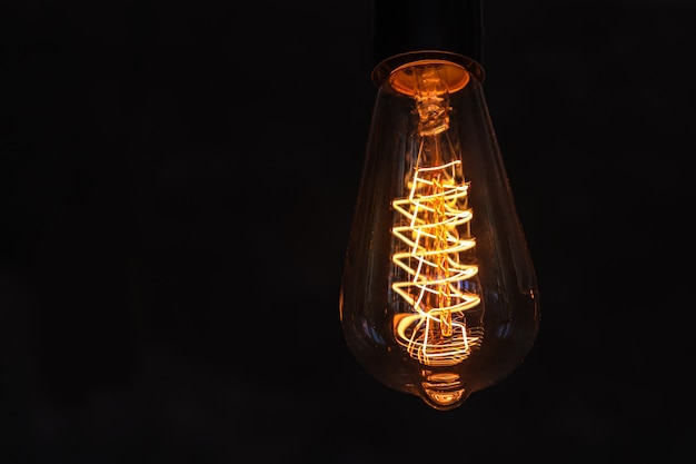 Vintage lightbulb on dark surface with bright yellow shining wire.