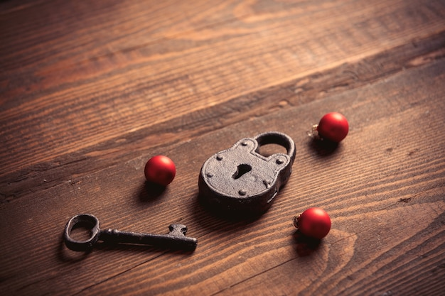 Vintage lock and key with christmas baubles on wooden table