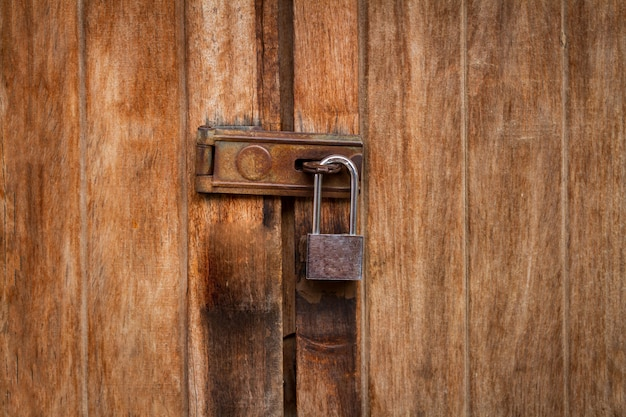 Vintage locked padlock with chain at brown wooden door background, closeup