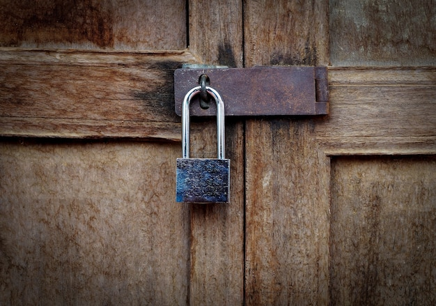 Vintage locked padlock with chain at brown wooden door background