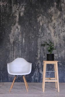 Vintage loft interior with wooden floor, textured aged grey concrete on the wall and chair