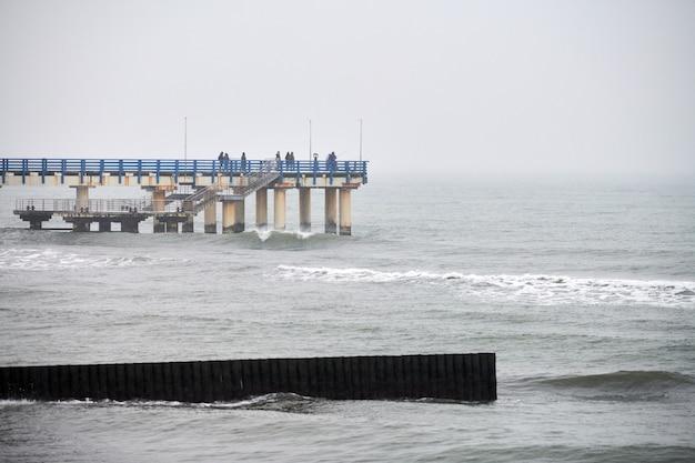 Старинные длинные деревянные волнорезы, уходящие далеко в море, зимний пейзаж балтийского моря