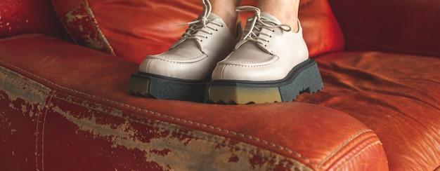 Винтажная роскошная мебель и современные городские кроссовки на девушке-подростке, баннер одежды образа жизни с красным креслом на фоне фото