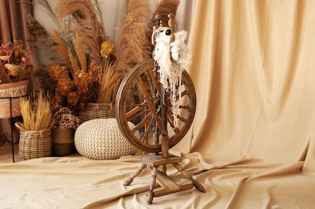 Старинный станок - шпиндель, устройство для ручного прядения пряжи. старое деревянное закручивая колесо с пряжей в деревянном домашнем интерьере. старинные инструменты и натуральная шерсть для изготовления экологической одежды. деревенский, бохо