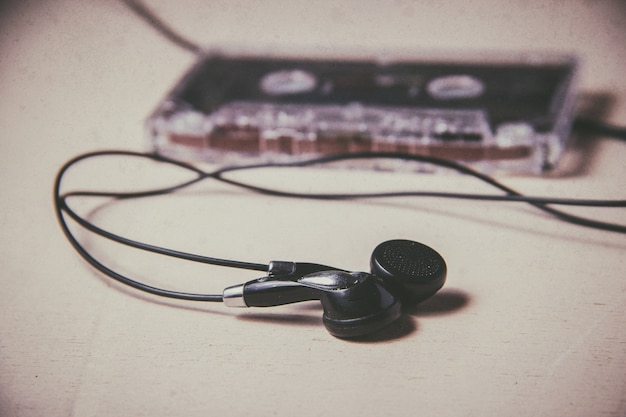 Vintage magnetic audio cassette and headphones on the wooden floor