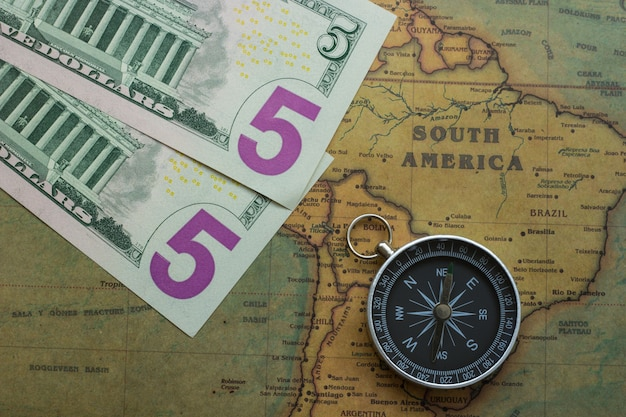 Vintage map of south america with five dolor bills and a compass, close-up