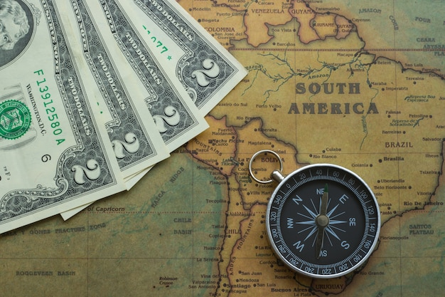 Vintage map of south america with two dolor bills and a compass