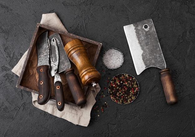 ヴィンテージの肉ナイフとフォークと黒いテーブルの上の古い木箱に手斧