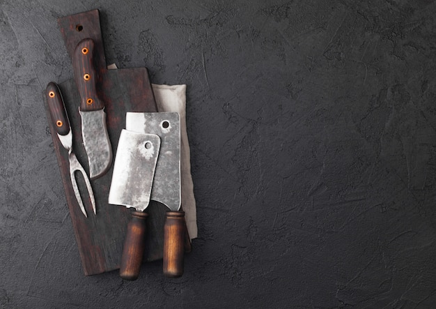 Vintage meat knife and fork and hatchets with vintage chopping board and black table.