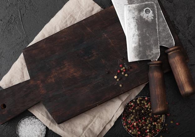 Винтажный топорик ножа мяса на винтажной прерывая доске и черной каменной предпосылке таблицы. мясная посуда.