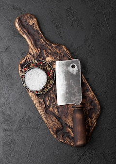 Vintage meat knife hatchet on vintage chopping board and black stone