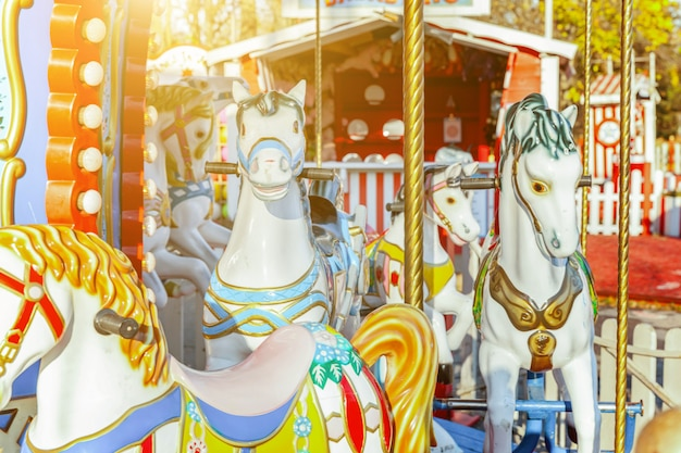 Vintage merry-go-round flying horse carousel in amusement holiday park