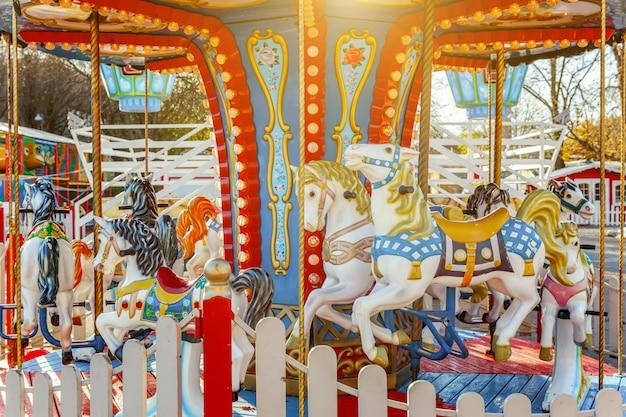 遊園地の休日の公園でビンテージメリーゴーランドフライングホースカルーセル