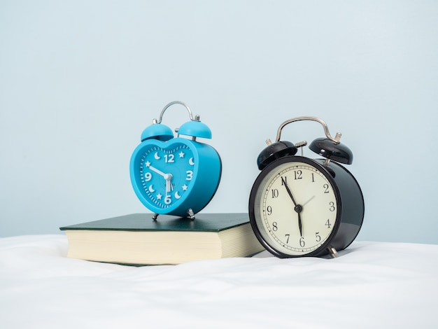 The vintage metal alarm clock on  the bedroom shows time in hour