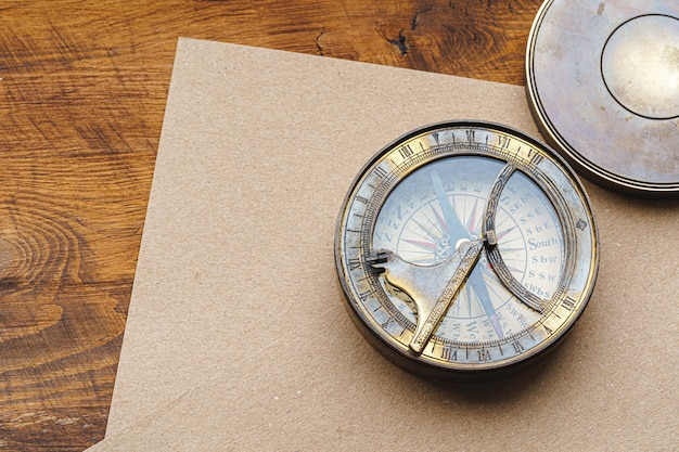 Vintage metal compass on carton paper on wooden table close up