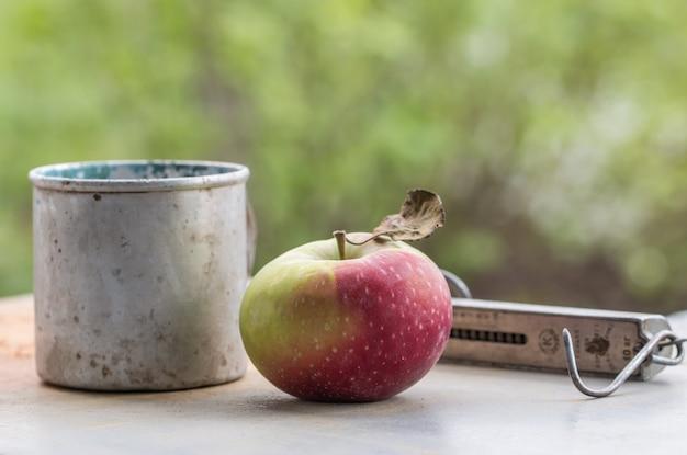 ヴィンテージの金属製のカップとリンゴ