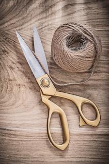 Vintage metal golden scissors hank of rope on wooden board