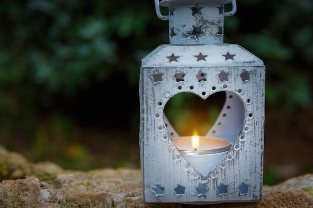 Vintage metal heart shape candle holder lit burning flame standing on stone in garden