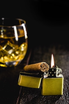 Vintage metal lighter with whiskey glass and cigar.