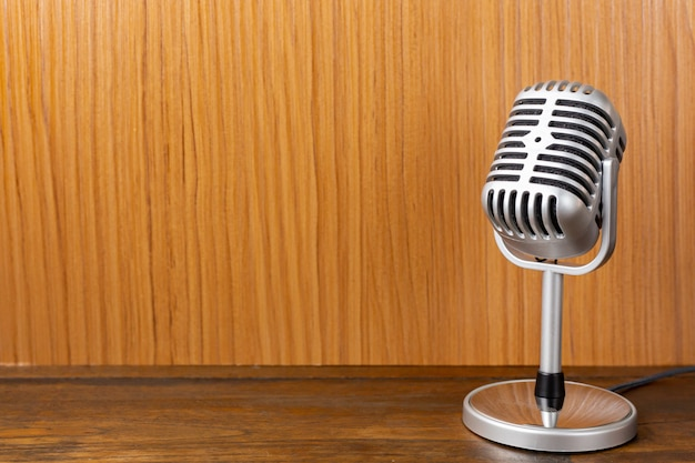 The vintage microphone close up image on wood background.