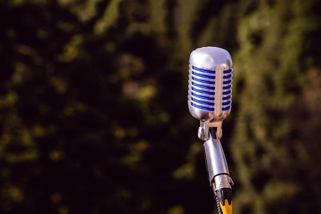 Винтажный микрофон, металлический ретро-стиль с лесом или природой на поверхности, концепция живого шоу