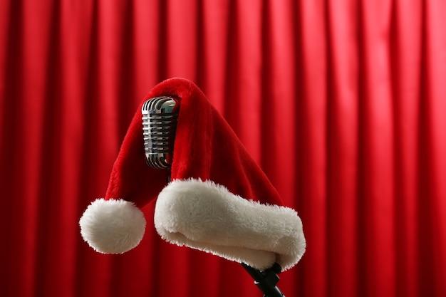 赤いカーテンの表面にクリスマスの帽子とヴィンテージマイク