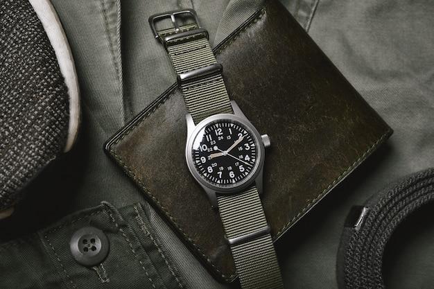 육군 녹색 배경에 나토 스트랩과 가죽 지갑이 달린 빈티지 밀리터리 시계, 클래식 시계 기계식 손목 시계, 밀리터리 남성 패션 및 액세서리.